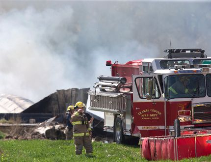 A firefighter wipes his brow while battling a fire Wednesday at 6097 Cobble Hills Rd. near Thorndale that destroyed the Smith family barn. (DEREK RUTTAN, The London Free Press)