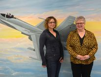 Linda Dunn, right, museum curatorial manager and Jennifer Ross, left, Air Force Museum Curator, pose in front of a mural depicting a CF18 at Cold Lake Museums