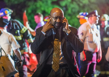 Philadelphia Mayor Michael Nutter speaks on a mobile phone as emergency responders search for passengers following an Amtrak train derailment in the Frankfort section of  Philadelphia, Pennsylvania, May 12, 2015. REUTERS/Bryan Woolston