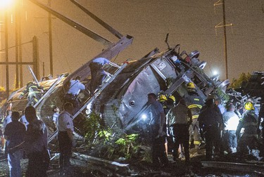 Rescue workers search for victims in the wreckage of a derailed Amtrak train in Philadelphia, Pennsylvania May 12, 2015.  An Amtrak passenger train with more than 200 passengers on board derailed in north Philadelphia on Tuesday night, killing at least five people and injuring more than 50 others, several of them critically, authorities said. Authorities said they had no idea what caused the train wreck, which left some demolished rail cars strewn upside down and on their sides in the city's Port Richmond neighborhood along the Delaware River. REUTERS/Bryan Woolston      TPX IMAGES OF THE DAY