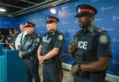 Toronto Police Service announces the body-worn cameras pilot project at police headquarters in Toronto, Ont.  on Friday May 15, 2015. Const. Neil Robinson, (from front to back) Const. Ben Seto and Sgt. Jeff Redden pose with the new cameras.  Ernest Doroszuk/Toronto Sun
