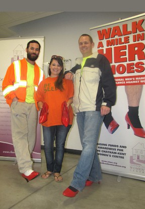 DuPont Pioneer employees Josh Reaume, left, and Ian Rumble, try on red high heels to help promote the Walk a Mile in Her Shoes event taking place in Chatham on May 31. Also pictured is Sole Sister Julie Russell who is organizing the Pioneer team for the fundraiser for the Chatham-Kent Women's Centre.(Blair Andrews/Chatham This Week)