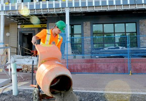 Justin Gagnon, of the firm Huyer Enterprises, drains water and concrete from a mixer as workers continue on the ground floor of the Aquatarium in Brockville on Tuesday. (RONALD ZAJAC/The Recorder and Times)