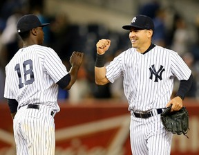 Didi Gregorius (18) and Jacoby Ellsbury of the New York Yankees celebrate their win over the Baltimore Orioles on May 8, 2015 at Yankee Stadium. (Elsa/Getty Images/AFP)