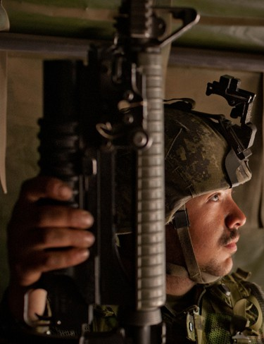 A soldier of the Royal 22nd Regiment looks out the back door of a troop carrier while being deployed to a new position during Operation Maple Resolve, Friday, May 15, 2015 in Wainwright, Alta. James Wood/Lloydminster Meridian Booster/Postmedia Network