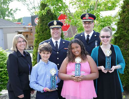 Jaden Chagnon (front row left), Serenity Rivers and Isabella Nie are winners of the second annual Children's Hero Awards presented by the Children's Safety Village of Brant. With them are Lisa Roddie (back row left), executive director of the safety village, Brantford Fire Chief Jeff McCormick, and Brantford Police Chief Geoff Nelson. (Submitted Photo)