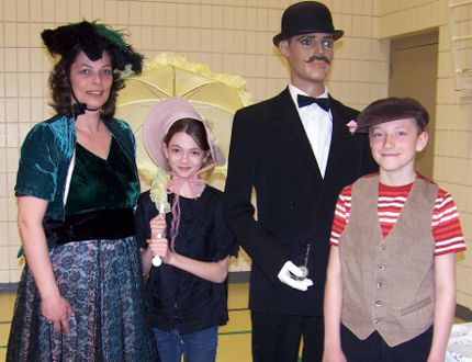 Plum Coulee Grade 6 teacher, Claire Goertzen gets in character with two Border Valley students in early 20th Century period costume.