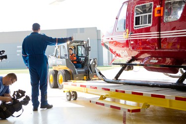 STARS pilot Andrew Davidson gives thumbs up as fellow pilot Jason Gaveline pulls a STARS air ambulance out from the hangar at the Winnipeg base during an open house Sat., May 23, 2015. (Brook Jones/Postmedia Network).