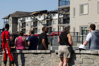 Residents wait for information as fire investigators work at a condo fire site at The Avenue condominium complex at 50th Street and Manning Drive in Edmonton, Alta., on Saturday May 23, 2015. A large fire broke out in the complex on May 22 in the evening. Ian Kucerak/Edmonton Sun/Postmedia Network