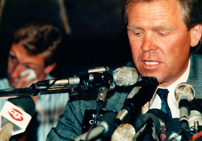 Aug. 9, 1988. Edmonton Oilers President, General Manager and Head Coach Glen Sather talks to the media as Ex-Edmonton Oilers superstar Wayne Gretzky wipes a tear in the background during the press conference at Molson House in Edmonton Alta., on Aug. 9, 1988. It was announced that Gretzky was traded (and sold) to the LA Kings by team owner Peter Pocklington. Edmonton Sun/QMI Agency