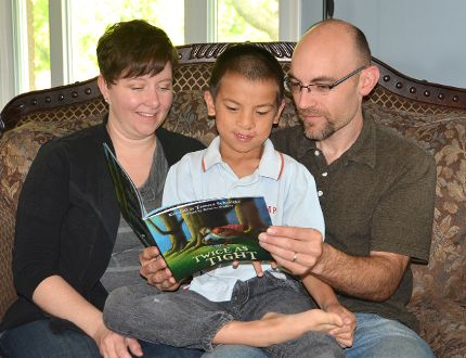 Tamara and Kendall Schmitke look at their book, Twice as Tight, with their adopted son Donovan, 8, at their home west of Springmount on Sunday