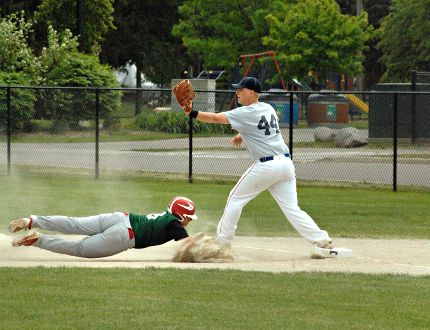 A St. John's College base runner dives back to first base during Monday's Brant County high school boys baseball championship game against Assumption College at George Henry diamond at Cockshutt Park. (Expositor Photo)