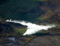 A water bomber dumps its load on the wildfire 22 km east of Slave Lake along the Old Smith Hwy near Mortonville on May 26, 2015. Many residents have been permitted to return home, but the province-wide fire ban remains in place. Alberta Wildfire Info/Postmedia Network