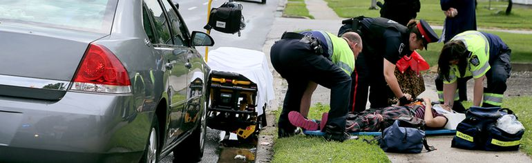 A woman is attended to by paramedics and a police officer after being hit by a vehicle on Grand Avenue West in front of the Chatham-Kent Health Alliance Wednesday afternoon. Police said the woman was conscious and talking when she was transported to hospital. The police said the crash is under investigation. Photo taken in Chatham, Ont. on Wednesday May 27, 2015. (Diana Martin/Chatham Daily News/Postmedia Network)
