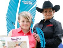 Inaugural Blue Feather art contest winner Marley Kelsey, 10, is presented with her award by Phyllis Finch on Wednesday at the Blue Feather event at the Stompede in Evergreen Park. Tom Bateman/Daily Herald-Tribune