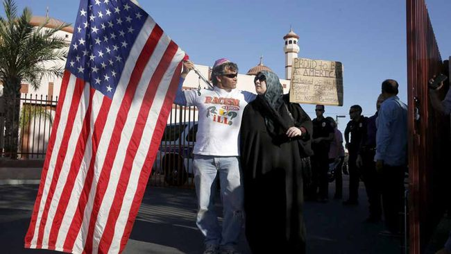 "Two demonstrators stand in front of the Islamic Community Center to oppose the ""Freedom of Speech Rally Round II"" across the street in Phoenix, Arizona May 29, 2015. Arizona police stepped up security near a mosque on Friday ahead of a planned anti-Islam demonstration featuring displays of cartoons of the Prophet Mohammad, weeks after a similar contest in Texas came under attack from two gunmen.  REUTERS/Nancy Wiechec"