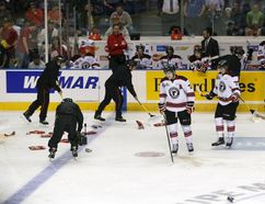 Workers clean the ice after fans threw garbage during the second period of the semi-final Memorial Cup hockey game between the Quebec Remparts and the Kelowna Rockets at the Colisee Pepsi on May 29, 2015. (REUTERS/Mathieu Belanger)