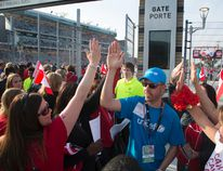 UNICEF Canada team members high-five amongst themselves and with fans arriving for the Women's World Cup Soccer friendly match between Canada and England at Tim Horton's Field in Hamilton, Ontario on May 29, 2015. (Peter Power/UNICEF Canada)