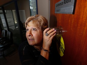 Sun columnist Sue-Ann Levy tries to listen through the door to the TCHC finance and audit committee's closed-door session on Thursday May 28, 2015. (Stan Behal/Toronto Sun)