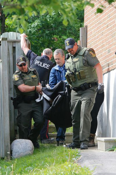 York Regional Police and Ministry of Natural Resources officers remove the dead bear from a Newmarket resident's back yard. (DAVE THOMAS/Toronto Sun)