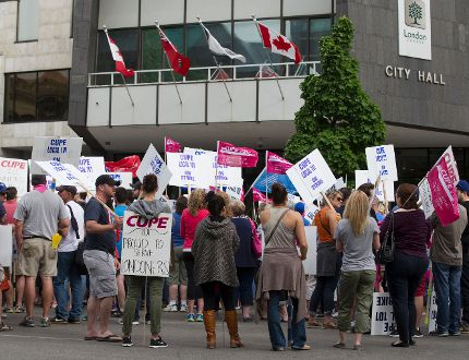 Some of London's 750 inside city workers rally outside of city hall on the first day of their strike in London, Ont. on Monday May 25, 2015. (DEREK RUTTAN, The London Free Press)