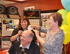 Smitty's Fine Furniture president Bob Gray getting the finishing touches from Smitty's employee Gina Williams and Hanover mayor Sue Paterson.