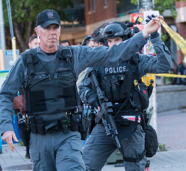 """Ottawa police hostage negotiators, tactical unit officers and patrol officers were dealing with a """"confrontational"""" man, possibly armed with a knife, who threatened police near Bank Street and MacLaren Strteet in downtown Ottawa on Tuesday June 2, 2015. Errol McGihon/Ottawa Sun/Postmedia Network"""