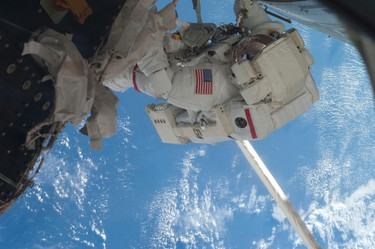 Flight engineer Mike Fossum works outside the International Space Station during the last spacewalk conducted with a space shuttle docked to the station in this photo provided by NASA and taken July 12, 2011.    REUTERS/NASA/Handout