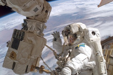 European Space Agency astronaut Christer Fuglesang of Sweden takes time out from his work to wave during his second spacewalk, with the earth in the background, in this digital still photo released by NASA December 15, 2006. REUTERS/NASA