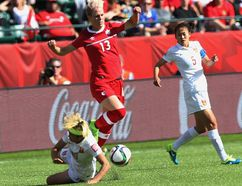 Canada's Sophie Schmidt jumps over a China player during FIFA Women''s World Cup at Commonwealth Stadium in Edmonton on Saturday June 5, 2015. (Perry Mah/Postmedia Network)
