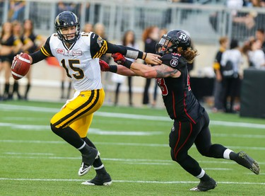Hamilton Tiger-Cats QB, Jeff Mathews, fights off Ottawa RedBlacks,Travis Brown, seconds before throwing first touch-down pass, at Tim Hortons Field, in Hamilton, Ont. on Monday, June 08, 2015. Dave Thomas/Toronto Sun/Postmedia Network