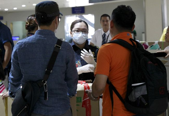 A customs inspector wearing a face mask talks to flight passengers from South Korea upon their arrival at the Ninoy Aquino International Airport in Manila, June 9, 2015. The World Health Organization said on Tuesday that the outbreak of the Middle East Respiratory Syndrome (MERS) in South Korea was the largest seen outside the Middle East, but it should not be a cause of concern. The South Korea's health ministry said on Tuesday there were eight new MERS cases reported, bringing the total of patients to 95.   REUTERS/Romeo Ranoco