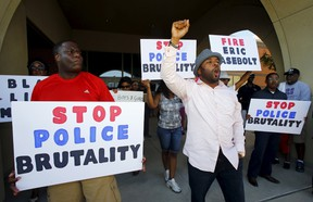 Protestors gesture and hold signs during a protest against what demonstrators call police brutality in McKinney, Texas June 8, 2015. Hundreds marched through the Dallas-area city of McKinney on Monday calling for the firing of police officer Eric Casebolt, seen in a video throwing a bikini-clad teenage girl to the ground and pointing his pistol at other youths at a pool party disturbance. REUTERS/Mike Stone