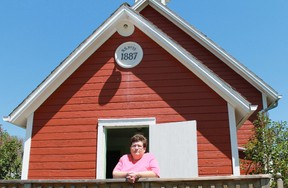 Moore Museum curator Laurie Mason stands in front of a one-room schoolhouse which was originally built in 1887. (File photo)
