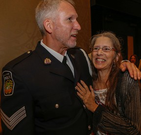 Peel Regional Police Acting Sgt. Mike Klarenbeek, who was shot in the Brampton courthouse last year, hugs Linda Hunt, who helped save his life, Tuesday June 9, 2015. (Dave Thomas/Toronto Sun)