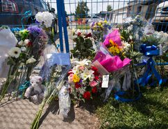 A makeshift memorial of flowers and cards is seen at 18620 62A Avenue in Edmonton, Alta., on Wednesday June 10, 2015. Const. Daniel Woodall was shot and killed executing a warrant at the house on June 8. Edmontonians have responded to the officer's death by laying flowers and signing books of condolence at sites across the city. Ian Kucerak/Edmonton Sun/Postmedia Network