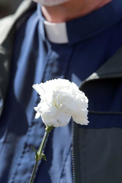 A minister carries a flower during a prayer walk organized by Our Saviour Lutheran Church in Edmonton , Alberta on Friday June 12, 2015. The walk include several churches is in honour of fallen police officer Daniel Woodall. Perry Mah/Edmonton Sun/Postmedia Network