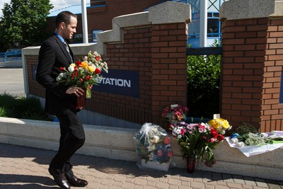 Flowers and cards dedicated to the memory of Edmonton Police Service Const. Dan Woodall are placed in front of the EPS West Division building at 16505 100 Avenue in Edmonton, Alta., on Tuesday June 9, 2015. Woodall was slain in a shootout in west Edmonton on June 8. Ian Kucerak/Edmonton Sun/Postmedia Network