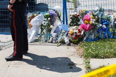 A police officer stands guard next to a makeshift memorial of flowers and cards at 18620 62A Avenue in Edmonton, Alta., on Wednesday June 10, 2015. Const. Daniel Woodall was shot and killed executing a warrant at the house on June 8. Edmontonians have responded to the officer's death by laying flowers and signing books of condolence at sites across the city. Ian Kucerak/Edmonton Sun/Postmedia Network