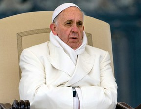 Pope Francis tries to keep himself warm as he attends his weekly general audience in St. Peter's Square at the Vatican in November 2013. (AP Photo/Alessandra Tarantino)