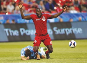 TFC forward Jozy Altidore gets tripped up by New York City FC defender Chris Wingert during Saturday night's game at BMO Field. (USA TODAY SPORTS)