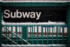 A snow covered subway sign is seen in New York's Times Square February 2, 2015. A huge winter storm hit the northeastern United States on Monday, the region's second snowy blast in less than a week, after leaving more than a foot (30 cm) of snow in the Chicago area. Up to six inches (15 cm) of snow was forecast for New York City, where the snow and ice caused a crowded subway train to stall on an elevated stretch of track.  REUTERS/Brendan McDermid
