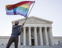 Vin Testa of Washington, D.C., waves a gay rights flag in front of the Supreme Court before a hearing about gay marriage in Washington in an April 28, 2015 file photo. The U.S. Supreme Court ruled on June 26, 2015, that the U.S. Constitution provides same-sex couples the right to marry in a historic triumph for the American gay rights movement. (REUTERS/Joshua Roberts/files)