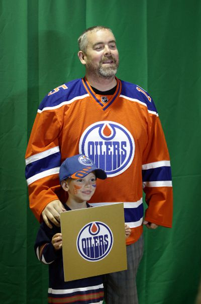 Al Hopwood and his son Ian gets their photo taken with the golden draft card at the Edmonton Oiler Draft Party at Rexall Place in Edmonton, Alberta Friday, June 26, 2015.Perry Mah/Edmonton Sun/Postmedia Network