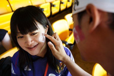 Japan fan Ken Usumi paints a heart with the Japanese flag on to Candy Kamide's face before a FIFA Women's World Cup 2015 match between Japan and Australia at Commonwealth Stadium in Edmonton, Alta., on Saturday June 27, 2015. Ian Kucerak/Edmonton Sun/Postmedia Network