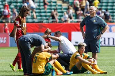 Australian players console each other after losing to Japan during a FIFA Women's World Cup 2015 match at Commonwealth Stadium in Edmonton, Alta., on Saturday June 27, 2015. Ian Kucerak/Edmonton Sun/Postmedia Network