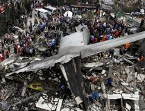 Security forces and rescue teams examine the wreckage of an Indonesian military C-130 Hercules transport plane after it crashed into a residential area in the North Sumatra city of Medan, Indonesia, June 30, 2015. At least 30 people were killed when the military transport plane crashed into a residential area two minutes after take-off in northern Indonesia on Tuesday, putting a fresh spotlight on the country's woeful air safety record. REUTERS/Roni Bintang