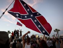 """Participants in the """"Ride for Pride"""" event stand on the back of their pickup truck as they speak to an assembled crowd during the impromptu event to show their support the Confederate flag in Brandon, Hillsborough County, June 26, 2015. Several hundred people took part in the event. REUTERS/Carlo Allegri"""