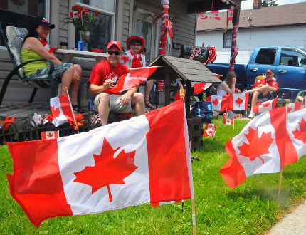 Monique Leclerc (seated right at table) is surrounded by friends and family on July 1 in Port Dover. The town becomes a sea of red and white every Canada Day. (DANIEL R. PEARCE Simcoe Reformer)