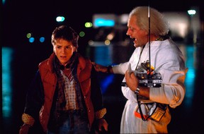 """This photo released by Universal Pictures shows, Michael J. Fox, left, as Marty McFly, and Christopher Lloyd as Dr. Emmett Brown, in a scene from the 1985 film, """"Back to the Future."""" Co-stars Lea Thompson, Lloyd and others gather on Tuesday, June 30, 2015, for a special screening of the 1985 Michael J. Fox time-travel blockbuster, to be presented on the massive Hollywood Bowl screen with musical score performed live and orchestra conducted by the original composer, Alan Silvestri. (Universal Pictures via AP)"""